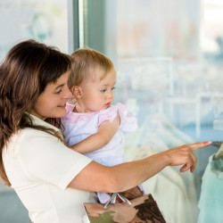 Mother with little girl in white dress looking through shop window